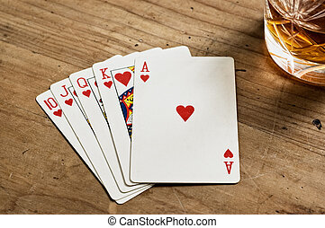 Poker cards and whisky glass on old wooden table.