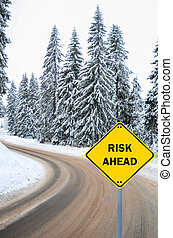 """RISK AHEAD"" sign against winter road"