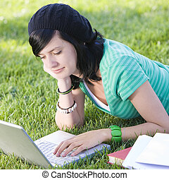 Happy teen in grass with laptop - Teen studies with laptop...