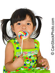 cute asian baby girl and big lollipop of thailand southeast...