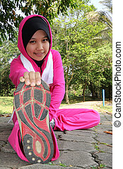A pretty muslim woman athlete stretching,exercising