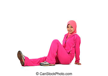 A pretty muslim woman athlete resting isolated on white