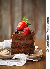Piece of chocolate cake with icing and fresh berry on wooden...