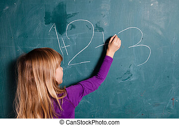 Young girl writing numbers on chalkboard