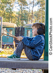 boy with headphone and drum sticks