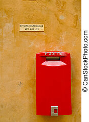 Red postbox on a yellow wall in Volterra, Tuscany, Italy...