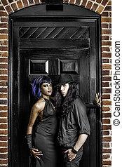 Gothic couple in front of door
