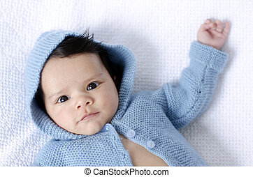 Newborn baby wearing blue cardigan - A newborn baby is...