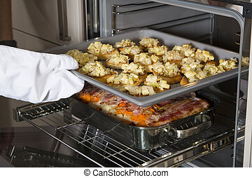 Crostini and casserole in the oven - a cook put crostinis...