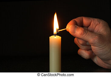 Hand and candle - Hand with lighting match and standing...
