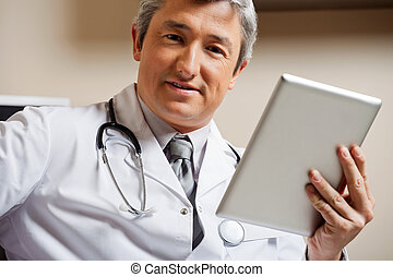Male Doctor Holding Digital Tablet - Portrait of mature male...