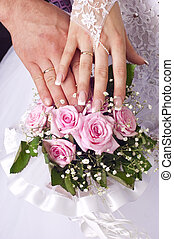 Wedding bouquet from tender roses, hands and rings