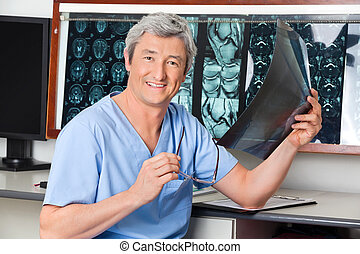 Happy Radiologist Holding X-ray - Portrait of mature male...