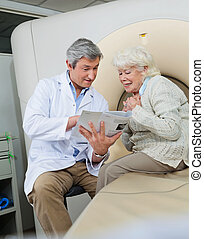 Doctor Explaining Female Patient - Mature male doctor with a...