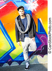 Full body shot of young man in front of graffiti