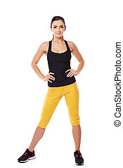 Fit woman athlete in gym clothes posing standing facing the...