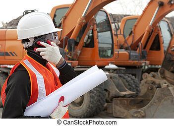 Construction worker with building plans and cellphone - road...