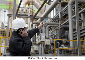 oil refinery engineer pointing against pipeline