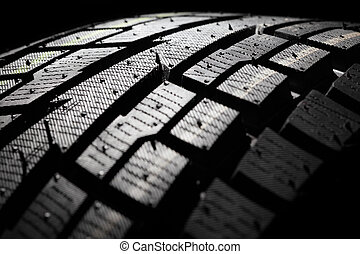 New winter tyre close-up. - New SUV winter tyre on a black...