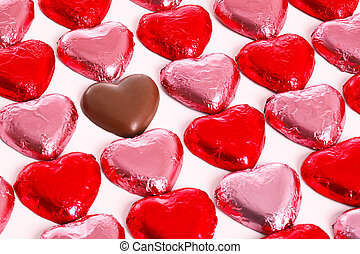 Chocolate hearts in red and pink foil wrappers on a white...