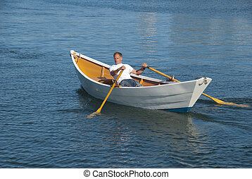 Man rowing a dory boat - Man rowing a new england dory in...