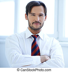 Handsome man standing with folded arms