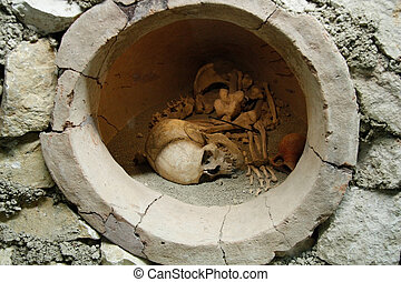 Skull and bones in ancient jar - Ancient human skull and...