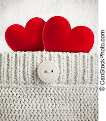 Two red hearts in wool pocket
