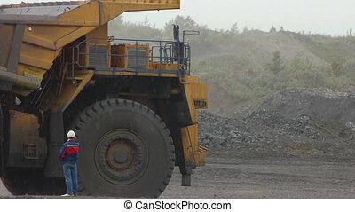 Mining dump trucks in the open pit mine, heavy truck in coal...