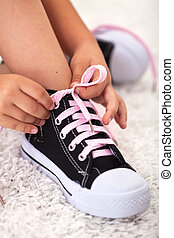 Child ties shoe - closeup on hands and sneakers