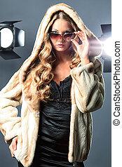 fur coat - Beautiful female model posing at studio in the...