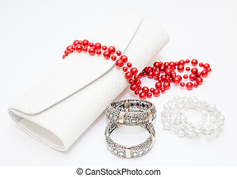 Golden braceletes red necklace with purse on white background