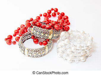 Two white gold braceletes and red necklace on white...