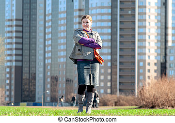Yuong woman full-length standing on field against building...