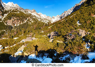 Winter mountains and shadow silhouette of a man