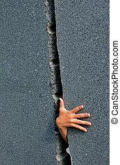 Breakthrough - a childrens hand reaching through a gap in...