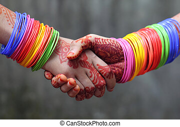 Shaking hands decorated with colorful bracelets and henna...