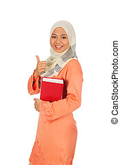 Beautiful young muslim women in thumb up action with a book. Isolated on white background.