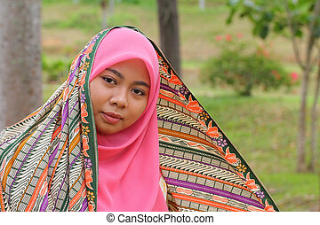 Close-up portrait of beautiful Muslim girl gazing steadily...