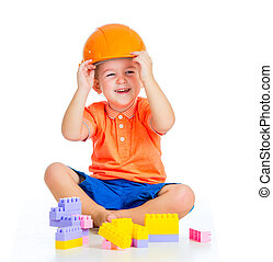 cheerful child boy with hard hat playing with building...