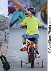First bicycle ride - Father is running behind his young son...