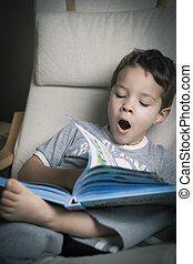 cute boy tired - little boy yawning while reading a book