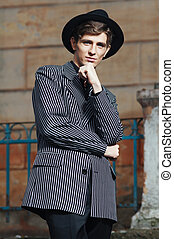 Retro styled fashion portrait of a handsome. Clothing and...
