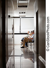 People In Hospitals Waiting Area - Group of people sitting...