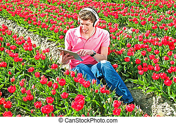 Young guy listening to music in a tulip field