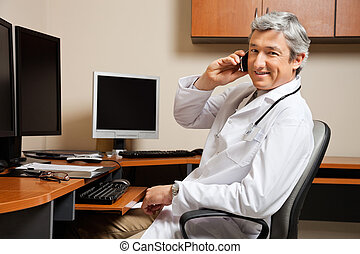 Happy Doctor On Call - Portrait of happy mature male doctor...