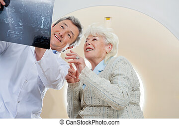 Doctor With Patient Looking At MRI X-ray - Mature male...