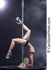 Young sexy woman exercise pole dance against a black...