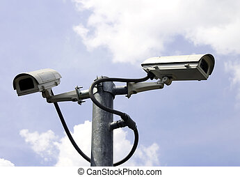 security cameras in front of blue sky
