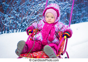 Small child is riding on a sled in the winter